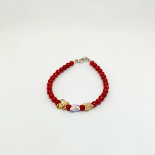 Slika prikazuje zlatnu narukvicu od crvenog koralja s leptirom od Swarovski kristala