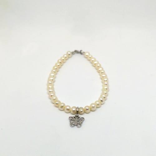 Slika prikazuje bisernu narukvicu od s privjeskom od bijelog zlata u obliku leptira