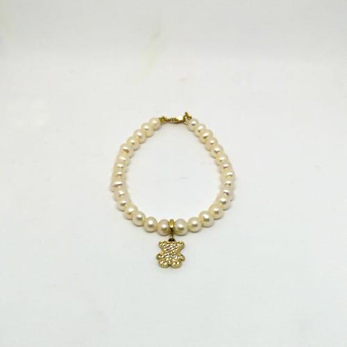 Slika prikazuje bisernu narukvicu sa zlatnim privjeskom medvjedića ispunjenog cirkonima